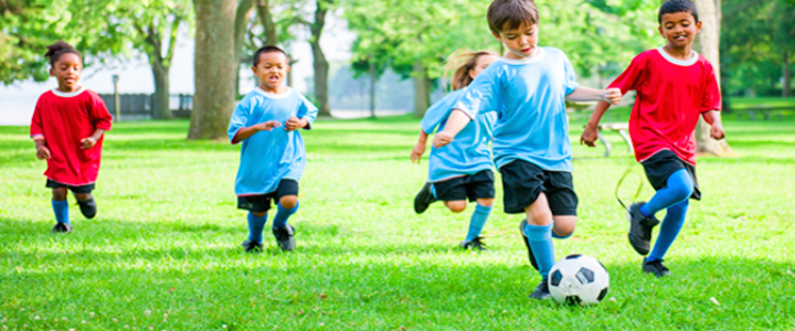 Young children playing soccer on a Vancouver community centre field.